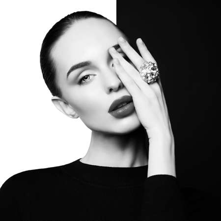 young sexy lady with big ring with diamonds in black-and-white studio. beautiful woman with perfect lips and black lipstick poses in photostudio. Fashion portrait of fashionable model. Stock Photo