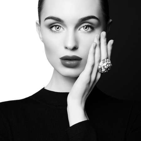 young sexy lady with big ring with diamonds in black-and-white studio. beautiful woman with perfect lips and black lipstick poses in photostudio. Fashion portrait of fashionable model. 版權商用圖片