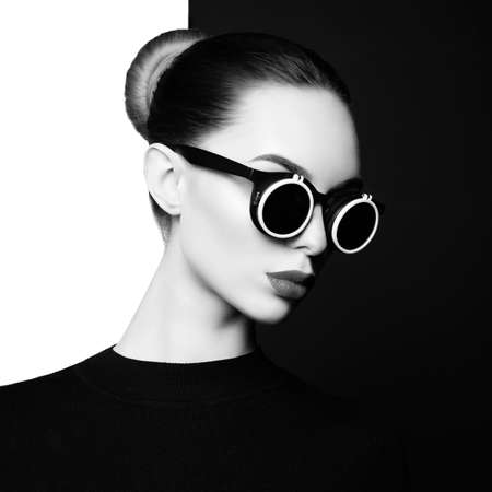 young sexy lady with black stylish sunglasses in black-and-white studio. beautiful woman with perfect lips and black lipstick pose in photostudio. Fashion portrait of fashionable model.