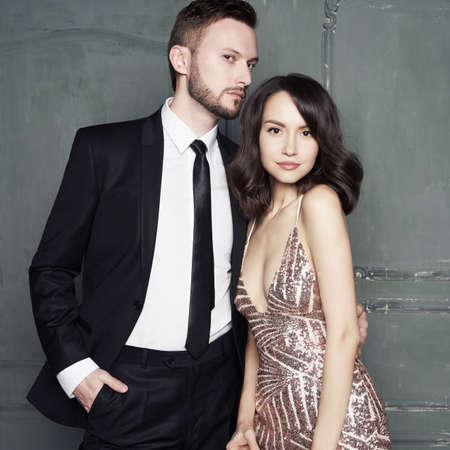Beautiful couple in evening dress and suit pose in classic gray interior. Glamour portrait of sexy young lovers. Fashionable elegant man and woman with stylish hairstyle.