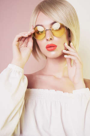 Beautiful sexy blonde with professional classic make-up pose in photography studio. Sensual stylish woman in erotic white dress. Blue-eyed lady with perfect lips in modern colour sunglasses