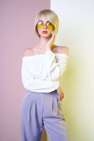 Beautiful sexy blonde with professional classic make-up pose in photography studio. Sensual stylish woman in blue pants. Blue-eyed lady with perfect lips in modern colour sunglasses
