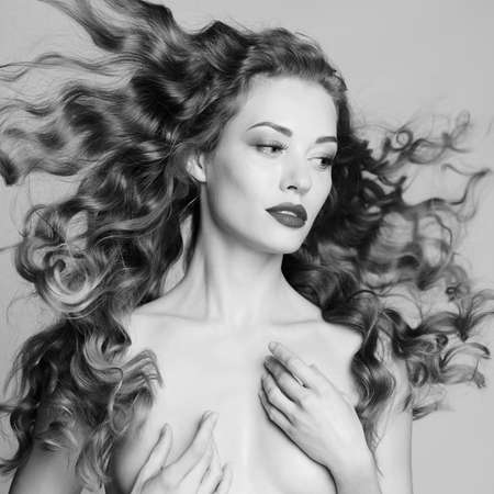 Black and white art portrait of sensual nude woman with elegant hairstyle on gray background