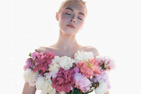Young beautiful woman with bouquet of roses. Art portrait of blonde with colorful flowers. Professional art makeup. Pretty girl isolated on white background.