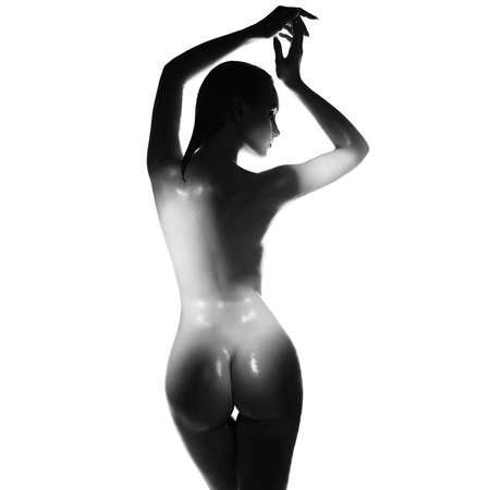 fashion art of elegant nude model in the light spotlights. sexual pose of young lady.