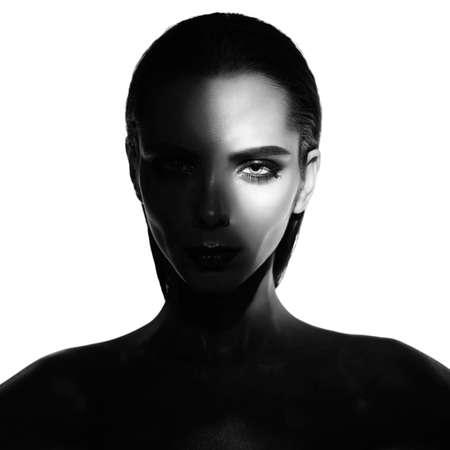 Portrait surréaliste de jeune femme avec du maquillage d'art. Photographie en noir et blanc de belles femmes avec des ombres à paupières smoky-eyes.