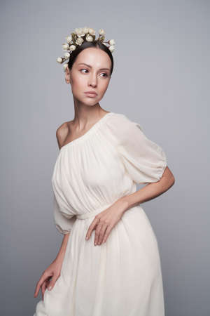 Fashion studio portrait of young beautiful woman in white greek dress with flowers on her head. Fashion and style Stock Photo