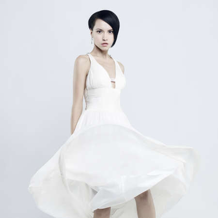 Fashionable photo of beautiful young lady in a billowing white dress