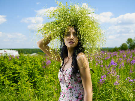 Young beautiful girl picks flowers in the field. A woman walks in a summer park.