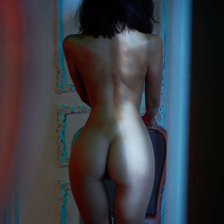 Beautyful nude woman in home interior. Sexy lady with perfect body in bedroom. Sexual portrait of young model pose infront of windows. Erotic figure of naked beauty in room.