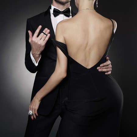 Fotografía conceptual de la elegante pareja en traje de noche y vestido. amantes del baile posan en el estudio de fotografía.