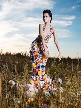 Fashion photo of beautiful lady in dress of flowers. Beautiful woman pose outdors.
