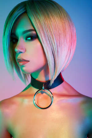 Fashion studio portrait of lovely asian woman with blonde short hair. Bright makeup. Fashionable haircut. Sexy young model in night club