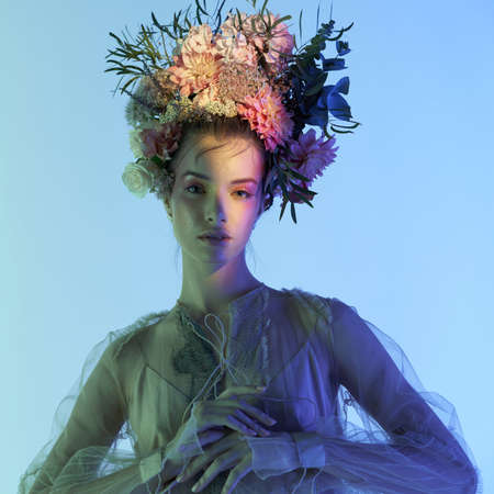 Fashion art photo of beautiful lady in flower diadem. Spring and summer portrait of young woman with real flowers in her hair. Standard-Bild
