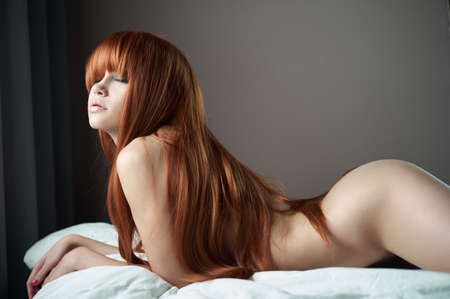 Fashion portrait of young sensual woman in bed. Redhead lady in bedroom. Nude sexy model pose in home interior. Naked beauty with long hair