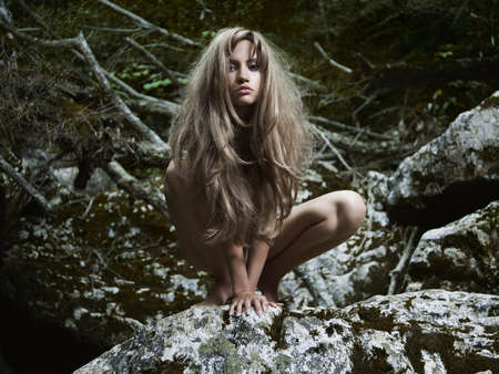 Portrait of a elegant lady in a green rainforest. Sexy young blonde woman pose outside. Standard-Bild