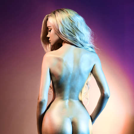 Nude beautiful blonde dancing in colorful light. Erotic portrait of sexy woman with long hairs. Sexual naked model pose on pink background. Perfect female body of elegant stripper. Standard-Bild