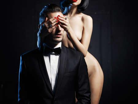Fashion studio photo of a sensual couple on black background Foto de archivo