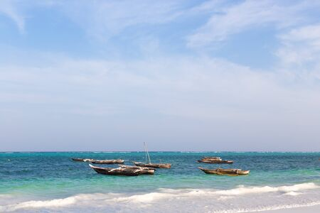ocean fishing: wooden fishing boat in the ocean surf on the island of Zanzibar on the blue sky background