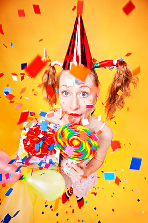 Girl with lollipop and gift, confetti flying around, all colorful, juicy. Stock Photo