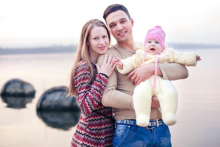Cute family on the shore of the lake. Mom hugs dad. Dad is holding a babygirl in his arms.