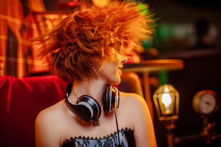 Roodharige meisje in koptelefoon met ongewone make-up in de disco