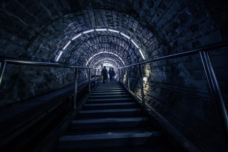 El tramo de escaleras: la gente sube los escalones, sus siluetas. Techo arqueado: un largo y estrecho corredor, el descenso a la mina de sal. Mina de sal - Solina Turda, Rumania. Foto de archivo - 83761388
