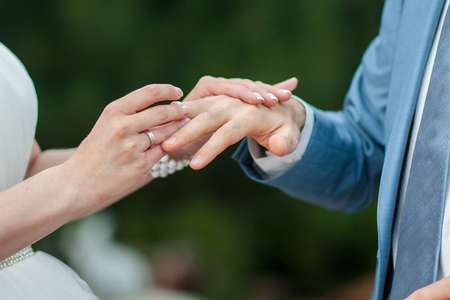 The bride puts a wedding ring on grooms finger. Large frame hands newlyweds.