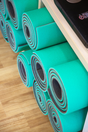 Exercise mats constricted, rolled-up on a shelf in the closet.