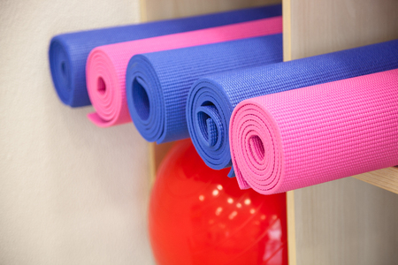 Yoga mats constricted, rolled-up on a shelf in the closet.