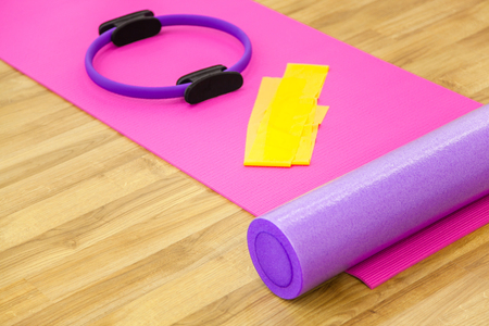 Roller, yoga mat, stability ring and yelow cloth on the parquet. Close-up shot. Archivio Fotografico