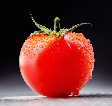 drop water: Juicy tomato with drops in the studio. Stock Photo