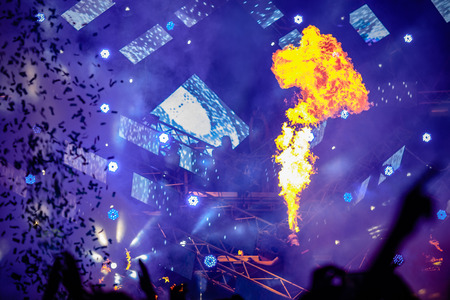 Fire show at the concert. Blue background, large screen monitor, confetti.