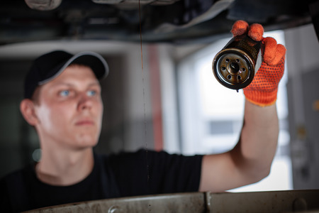 Specialist auto mechanic in the car service repairs the car. Replacing the oil filter. Stock Photo
