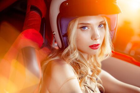 ruch: Sensual girl in helmet at the wheel of a sports car.