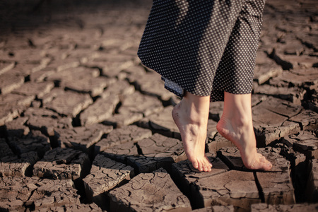 Heat shattered earth in the desert. Arid and sultry weather creates such beauty. Girl walks and stay on the cracked earth.