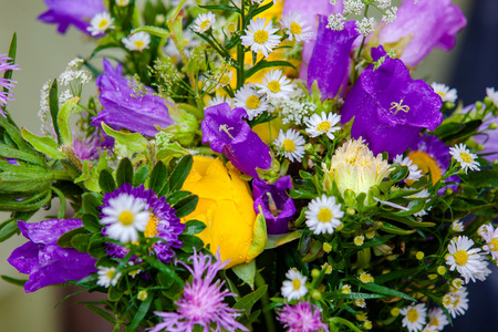 Bouquet of purple cornflowers, chamomiles and yellow roses. Close up photo.