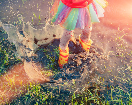 From above view of girl in gumboots and skirt splashing water standing in puddle and playing in sunset light. 版權商用圖片