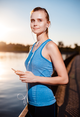 Active and beautiful girl in a blue sports t-shirt and black shorts, listening to music via the player in the mobile phone touch near the lake.