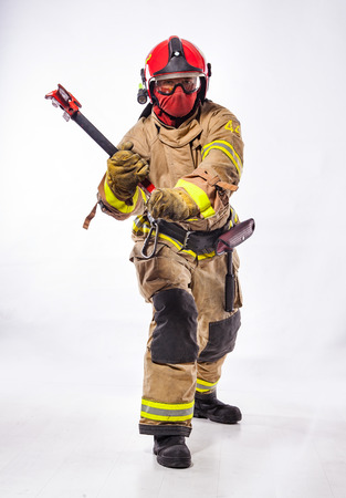 Anonymous fireman in uniform and protective helmet with glasses holding special ax looking at camera on white.