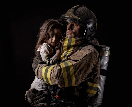 Dirty firefighter in uniform holding little saved girl standing on black background. Archivio Fotografico