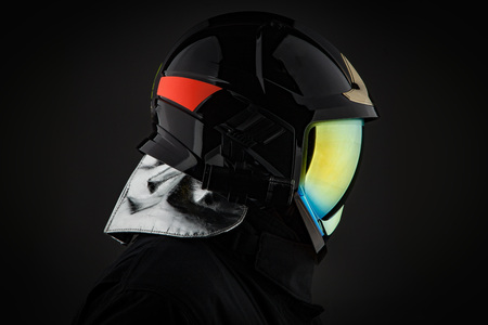 Side view of anonymous person wearing trendy minimalist protective helmet with shiny glass on black background. Archivio Fotografico