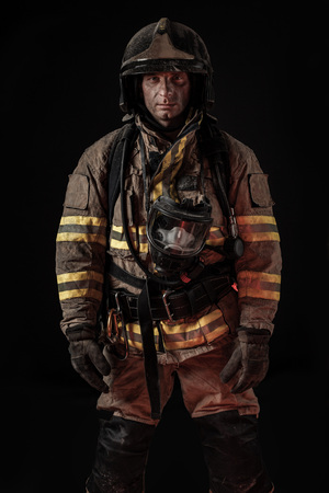 Serious dirty man in uniform of firefighter and helmet standing on black background looking seriously at camera.