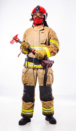 Man wearing costume of fireman with helmet holding ax and standing on white background looking at camera. Archivio Fotografico