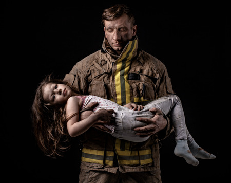 Serious firefighter in uniform holding little girl on hands looking at camera on black background. Archivio Fotografico
