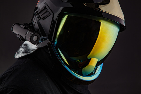 Unrecognizable man wearing stylish colorful helmet with protective glass standing on black background.
