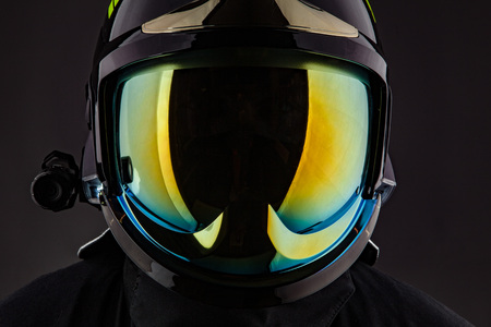 Minimalist shot of anonymous man wearing stylish modern helmet with colorful protective glass standing on black.