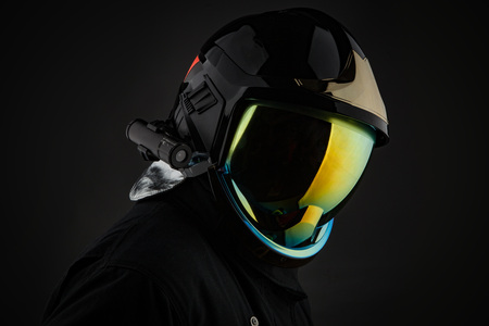 Person wearing trendy black helmet with colorful reflective protective glass on black background. Foto de archivo - 104833823