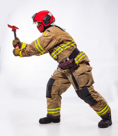 Side view of man wearing uniform and helmet of fire fighter and holding special ax standing on white background. Archivio Fotografico