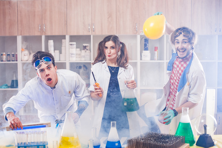 Cheerful male and female funny scientists standing in smoke and making experiments in lab. Archivio Fotografico